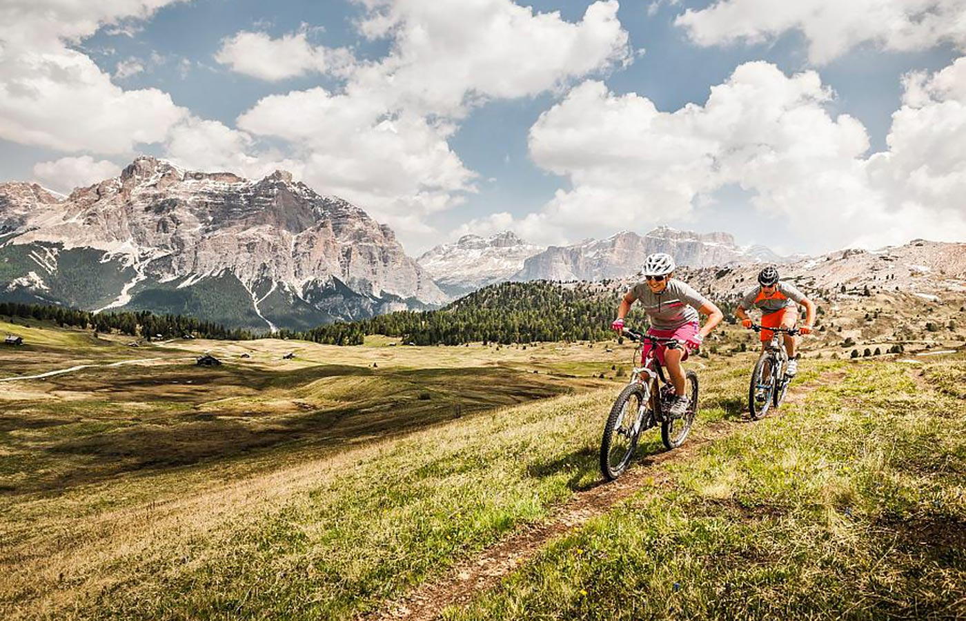 Mountain biker on a meadow with Dolomites in the background