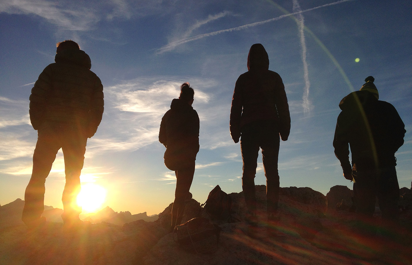 Group of hikers on a mountain peak at dawn