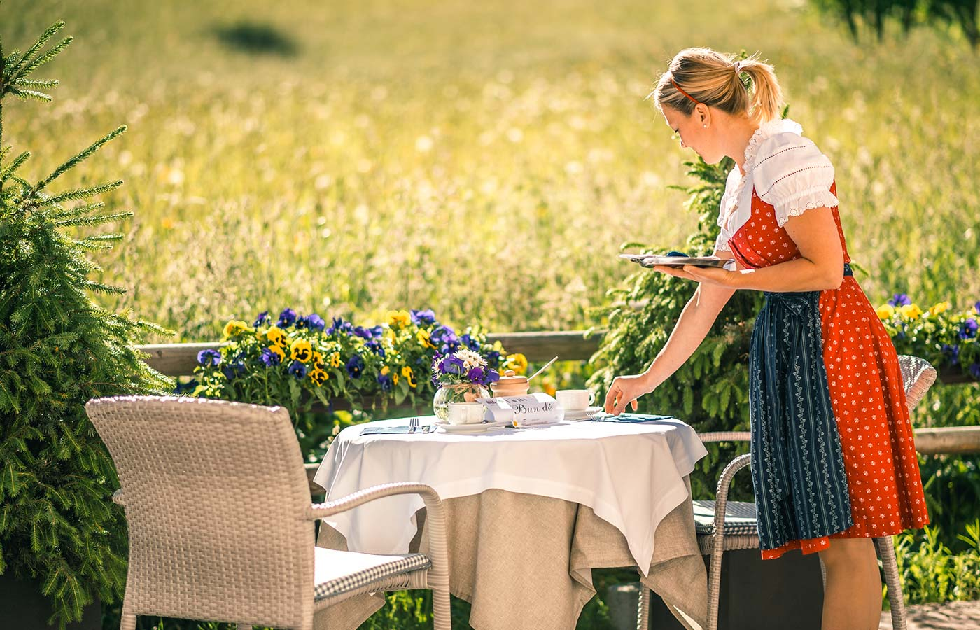 A waitress setting the table outside on a sunny day