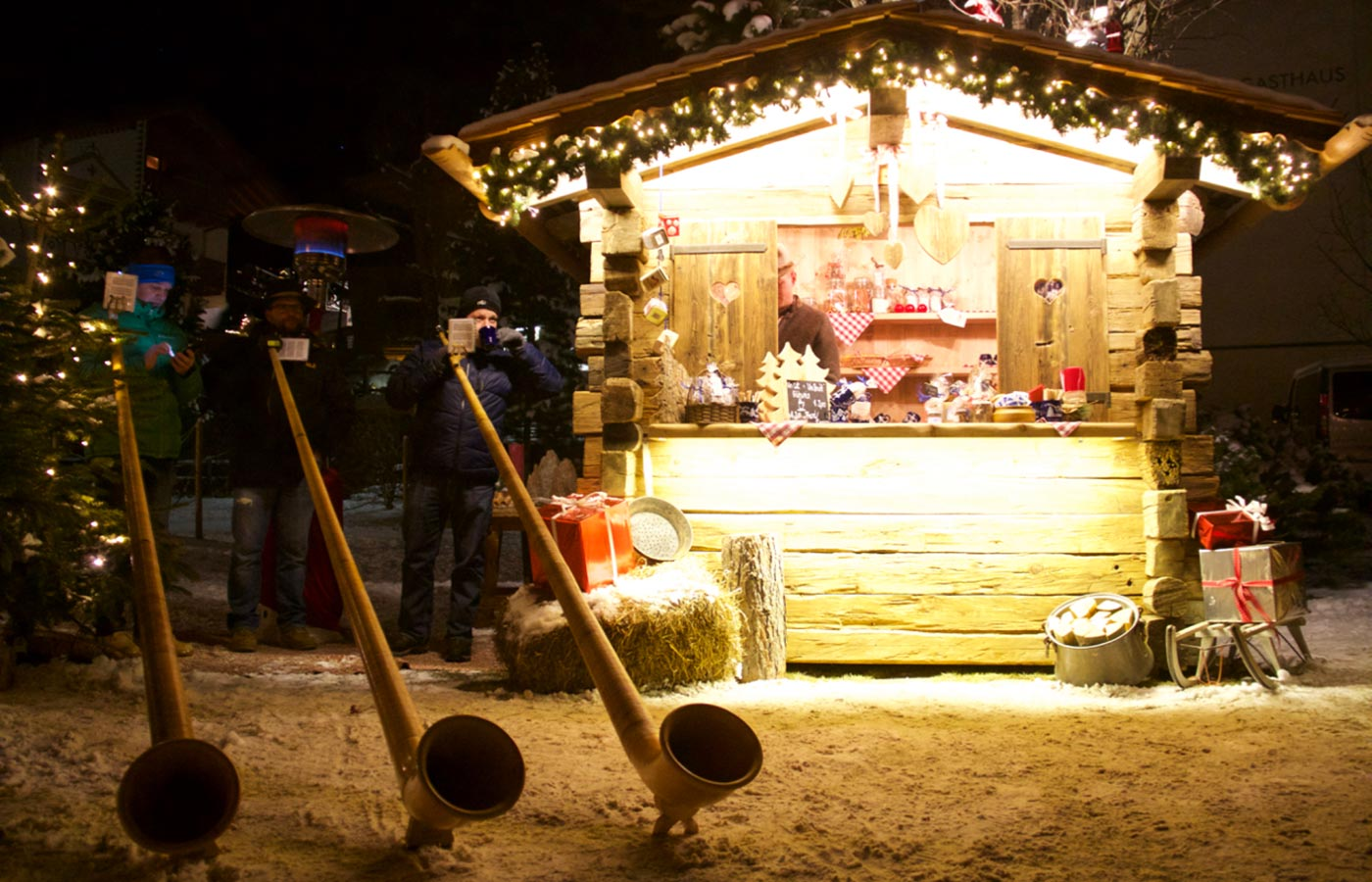 Alphorn players next to a Christmas stand in the snow
